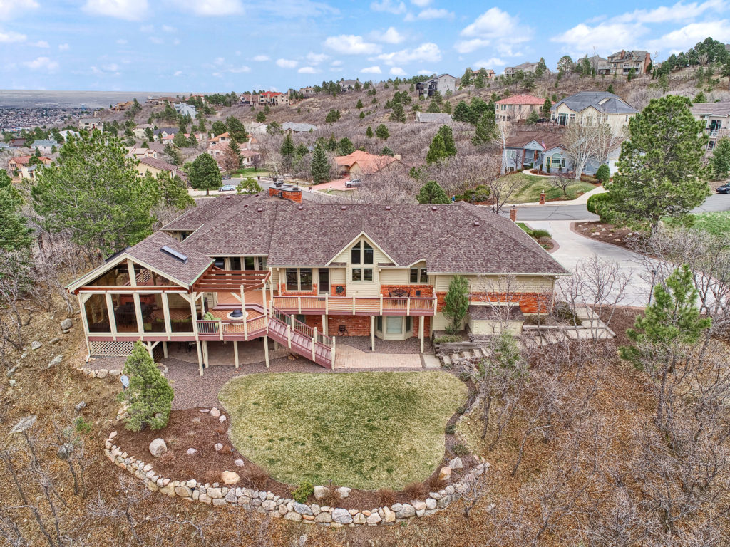 Elegant Broadmoor Hills home for sale with large windows and custom deck to enjoy the incredible mountain views.
